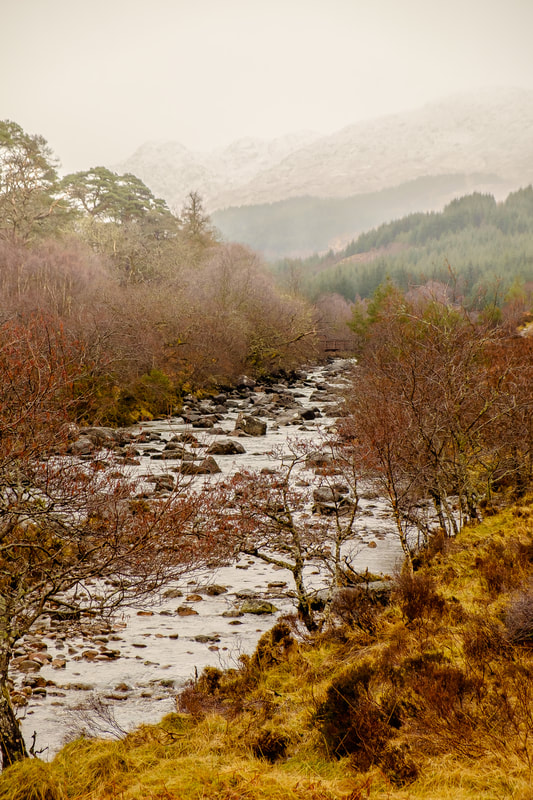 The River Strontian flowing through Ariundle Oakwood with the snow-covered peak of a misty Sgurr Dhomhnuill in the background | Sunart Scotland