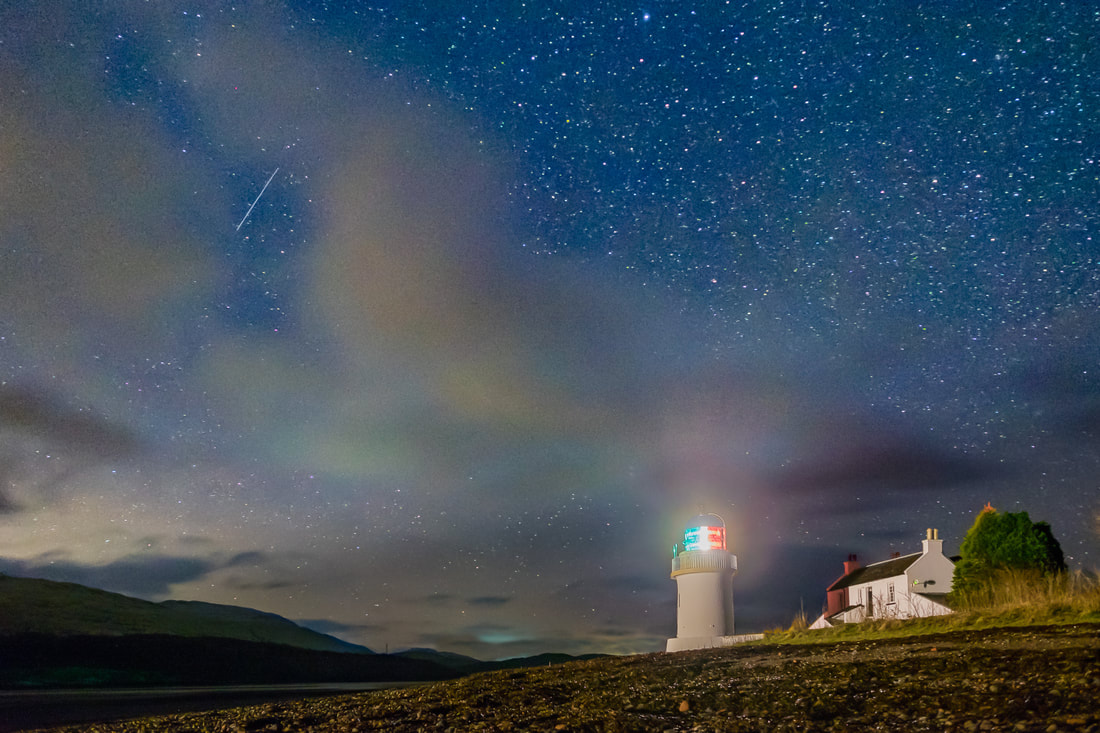 A single shooting star from the Quadrantids meteor shower flying across the sky above the Corran lighthouse and seen through a gap in the clouds | Ardgour Scotland