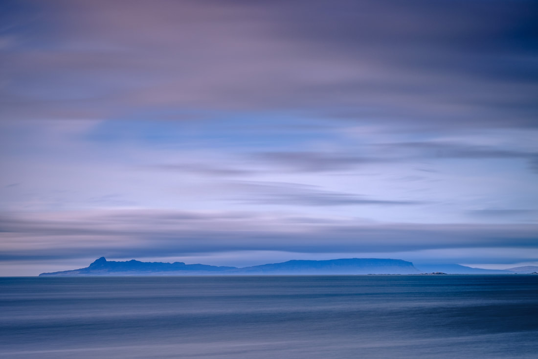 A rough sea and the fast-moving clouds are smoothed out by a long exposure in view cross the Sound of Arisaig to the Isle of Eigg | Moidart Scotland