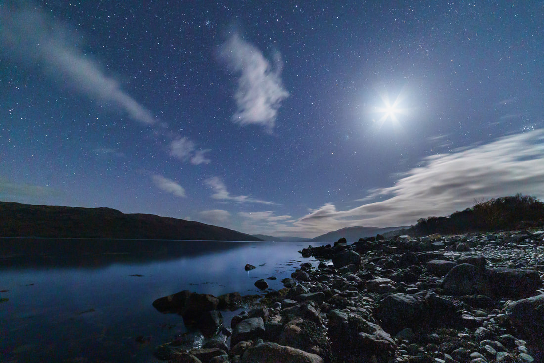 Rays of light bursting from the moon and lighting up the rocky shore of Loch Sunart | Sunart Scotland